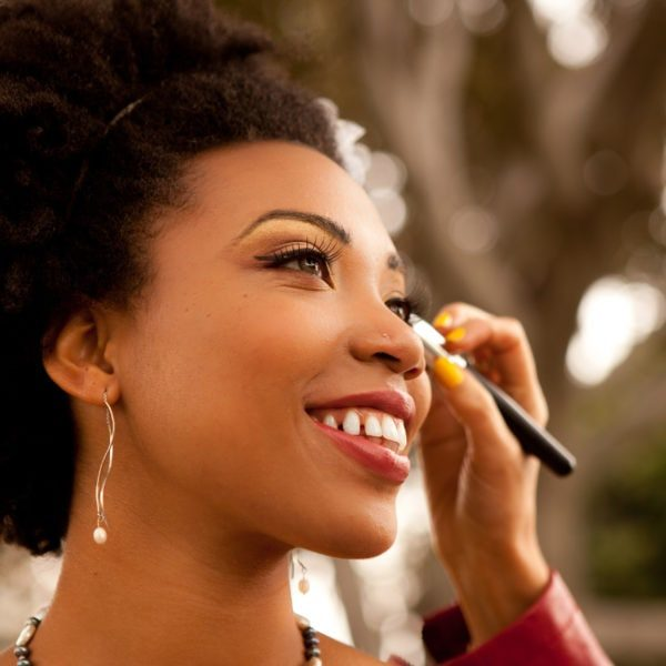 Profile of a Pretty African American Bride is smiling Getting Makeup retouched